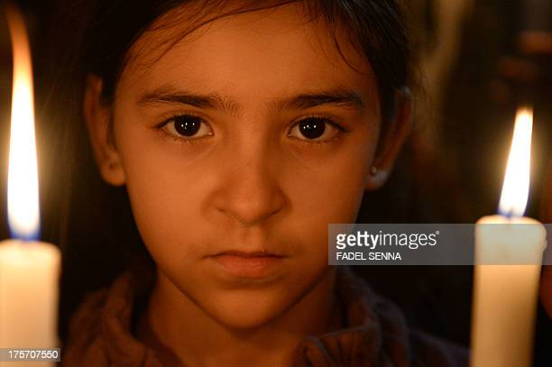 A young girl holds a candle duringduring a demonstration on August 6 2013 in Casablanca against the pardon by King Mohamed VI of Morocco to a Spanish...