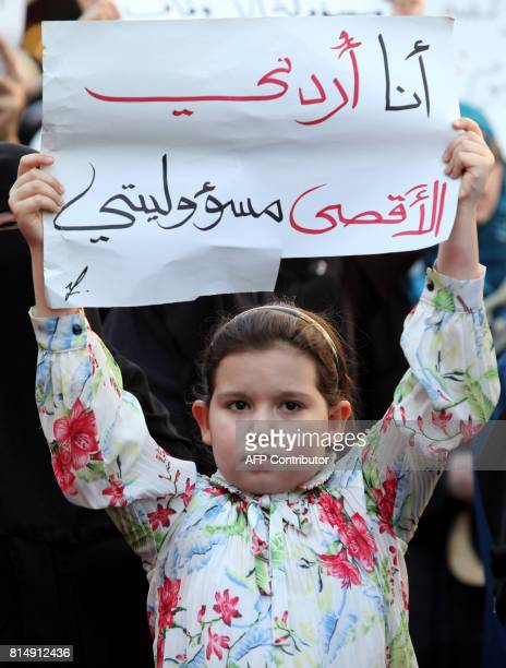 A young girl holds a placard reading in Arabic ''I'm Jordanian the AlAqsa is my responsibility'' in the Jordanian capital Amman on July 15 2017...