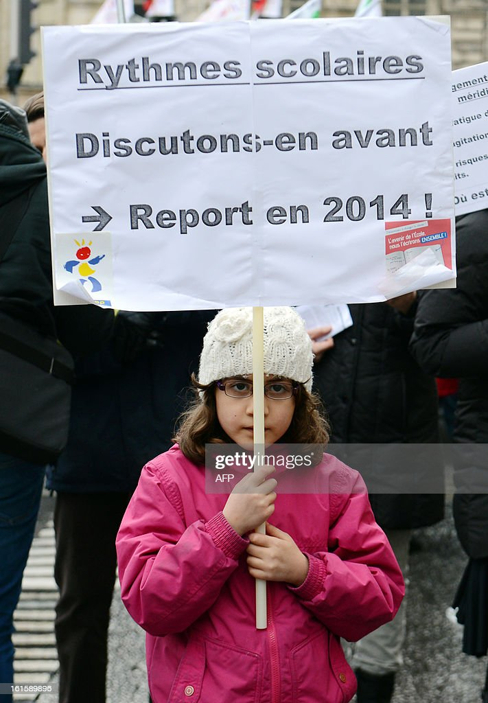 A young girl holds a placard reading 'School timetables : Let us discuss it before. Adjournment in 2014' as teachers, parents and children demonstrate on February 12, 2013 in Lyon, eastern France, as part of a nationwide strike day over the government's plans to make children attend classes five days a week, instead of the current four. The government recently issued a decree introducing a half day of school on Wednesdays for children 3 to 11 starting in September, while reducing the school day by 45 minutes the rest of the week.
