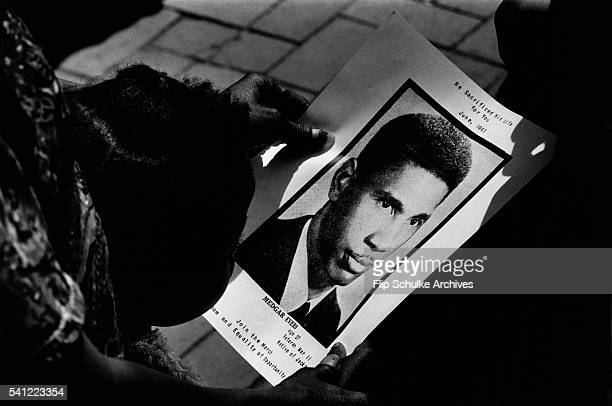 A young girl holds a program with a large photo of Medgar Evers at his funeral