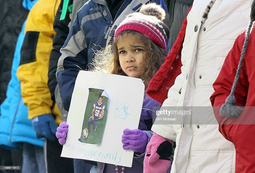 A young girl holds a sign that reads 'to Victor Cruz I was friends with Jack Pinto' and 'thanks New York Giants' as students, parents and faculty of Sandy Hook Elementary School as well as residents of Newtown, Connecticut attend the NFL game between the New York Giants and the Philadelphia Eagles at MetLife Stadium on December 30, 2012 in East Rutherford, New Jersey. Jack Pinto was a victim of the school shooting and was a big fan of the Giants Victor Cruz.The Giants defeated the Eagles 42-7.