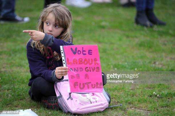 A young girl holds a sign which reads 'Vote Labour And Give Me A Future' as she waits for British Prime Minister Theresa May and Leader of the Labour...