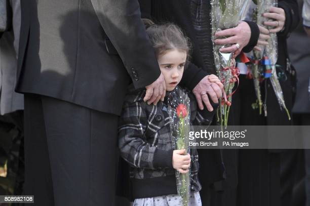 A young girl holds a single red rose as she waits on Wootton Bassett High Street for the repatriation of Corporal Stephen McKee of the Royal Irish...