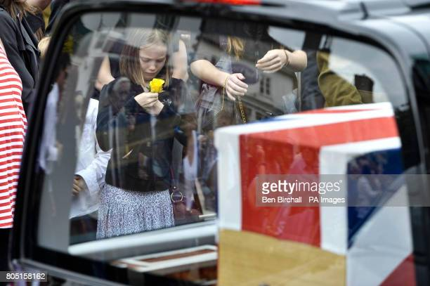 A young girl holds a single yellow rose as the second hearse as three pass through the town of Wootton Bassett during the repatriation of three...