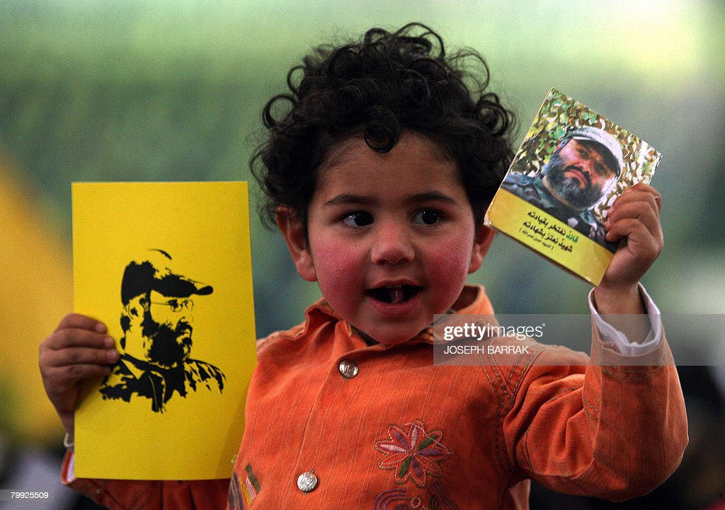 A young girl holds images of assassinated top Hezbollah commander Imad Mughnieh as she and her family gather in a street waiting to listen to a...