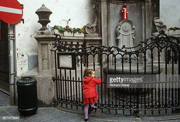 A young girl holds railings at the site of Brussels' famous landmark the Mannekin Pis statuette dressed in red A red theme appears from the...