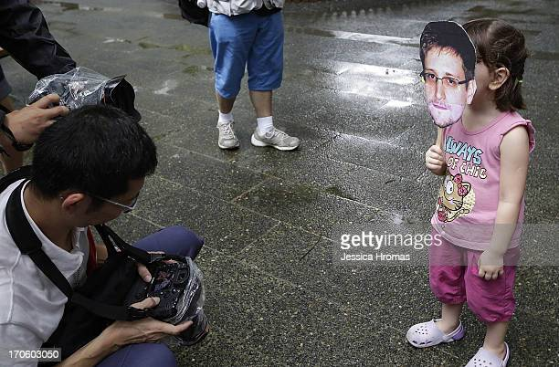 A young girl holds up a cut out image of Edward Snowdens face at the start of the protest rally to support Edward Snowden in on June 15 2013 in Hong...