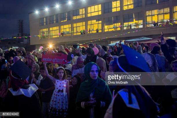 A young girl holds up a sign as University students from AlAzhar University arrive for their graduation ceremony on July 18 2017 in Gaza City Gaza...