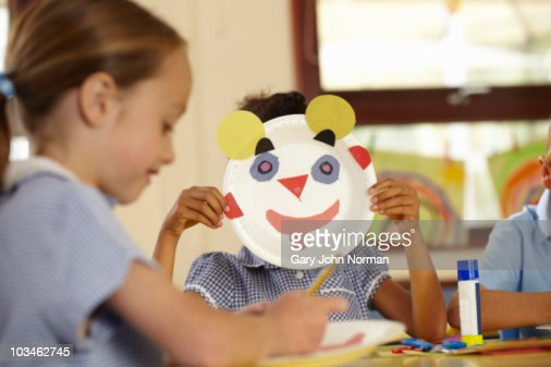 Young girl holds up painted face : Stock Photo