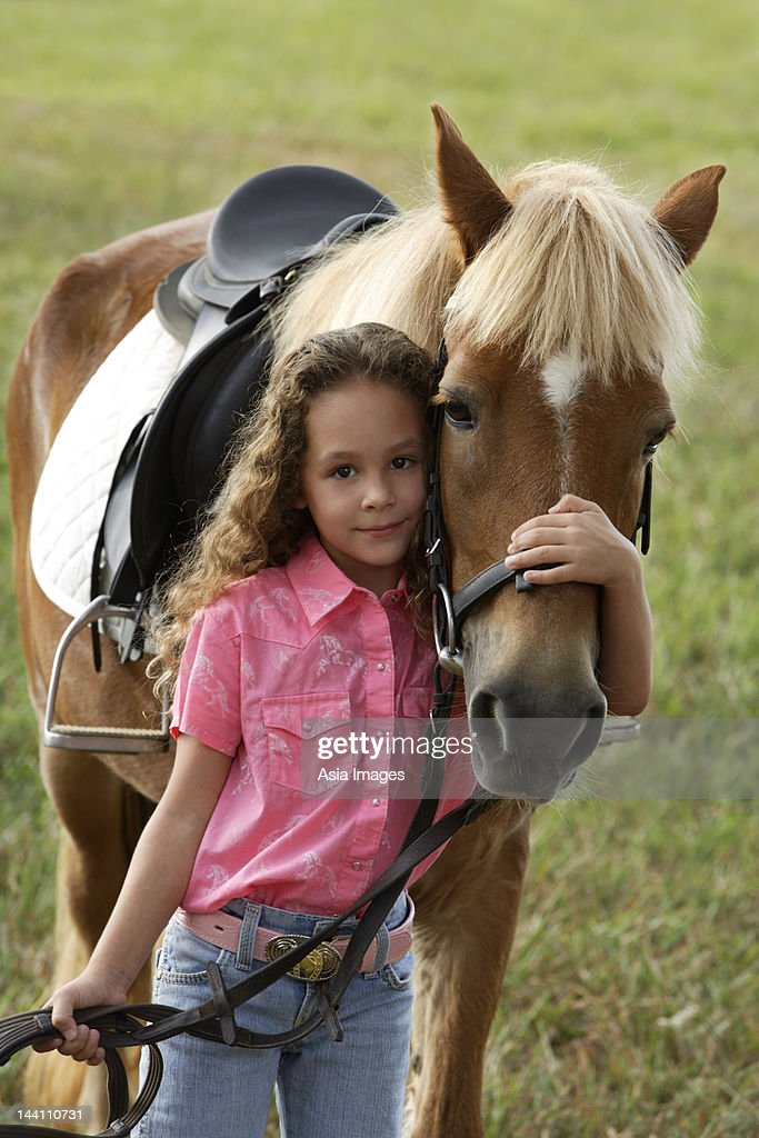 Young girl hugging nose of pony : Stock Photo