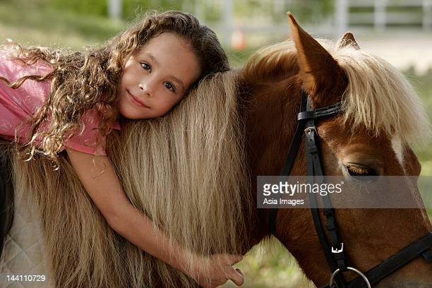 Young girl hugging pony