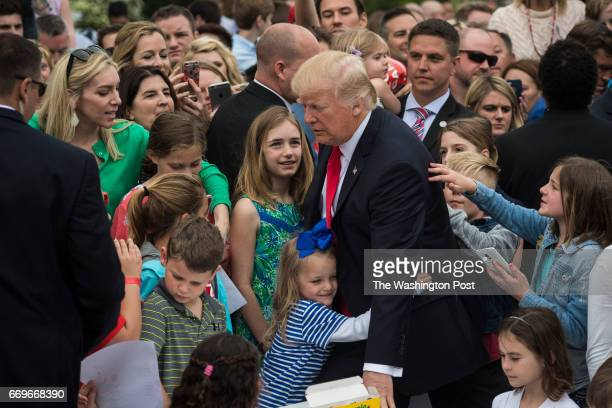 A young girl hugs President Donald Trump after makes cards for members of the military at a craft table during the 139th Easter Egg Roll on the South...
