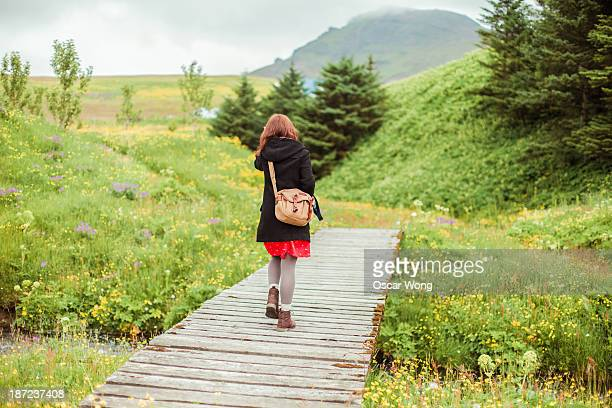 A young girl i crossing a wooden bridge