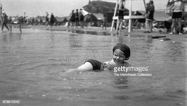 Young girl in a bathing costume and oversized swim cap lying in shallow sea water with groups of people on the shoreline at Atlantic City beach...