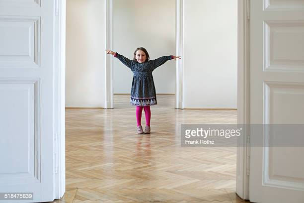 young girl in a big empty flat with wooden floor