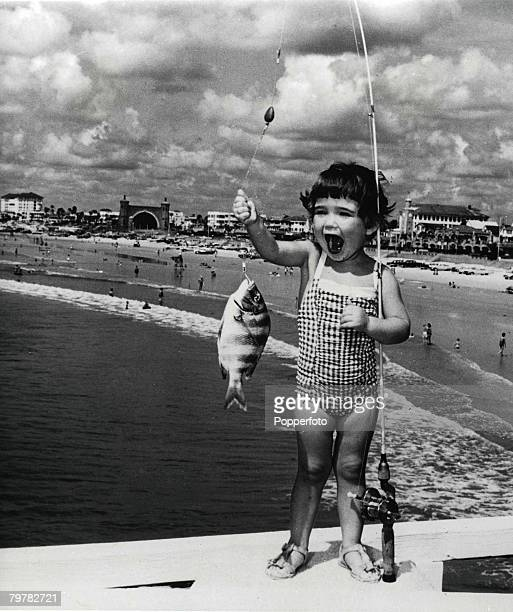 A young girl in a checked swimsuit her mouth wide open holding a fishing rod with a fish on the hook December 1963 A panoramic view of a Florida...