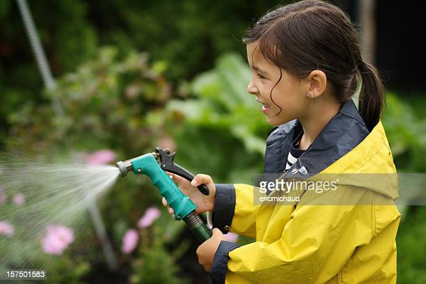 Young girl in a garden with hose pipe