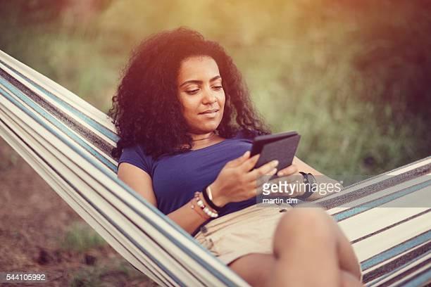 Chica joven en una hamaca y libro electrónico