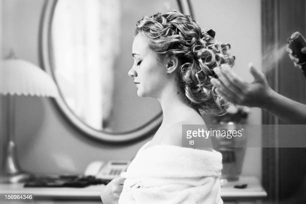 Young girl in a hotel room. Hairdresser makes hairstyle