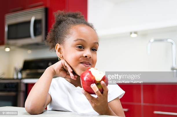 Young Girl in a kitchen, eating an apple.