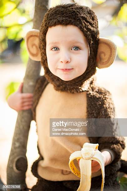 Young girl in a monkey costume sitting in tree eating banana