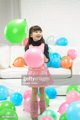 Young Girl in a Pink Dress Stands Holding One Balloon Among a Large Group of Balloons : Stock Photo