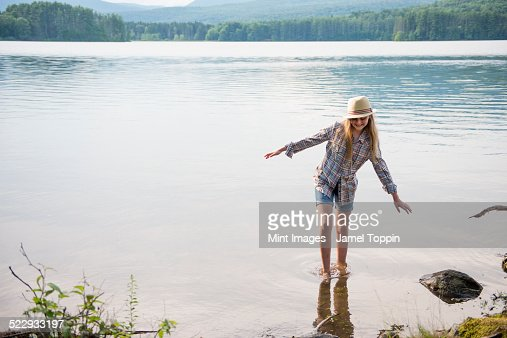A young girl in a straw hat and shorts paddling in the shallow waters of a lake.