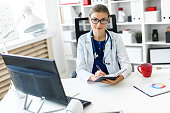 A young girl in glasses and a white coat is working in her office. photo with depth of field