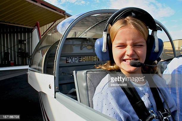 Young girl in an airplane, ready to fly
