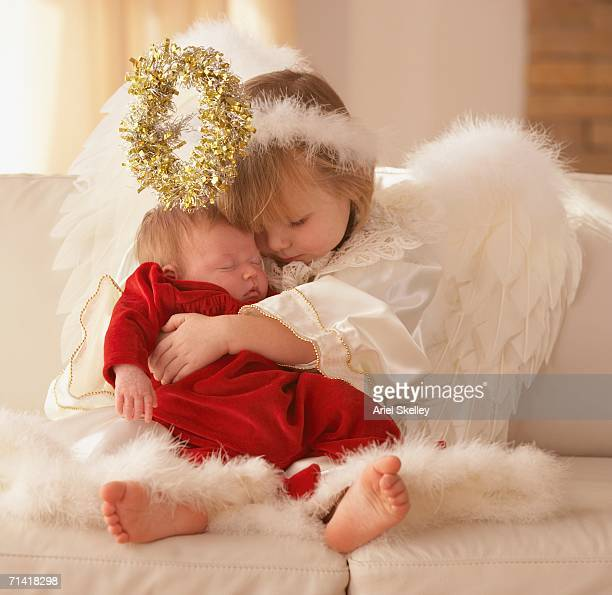 Young girl in angel costume hugging baby sister