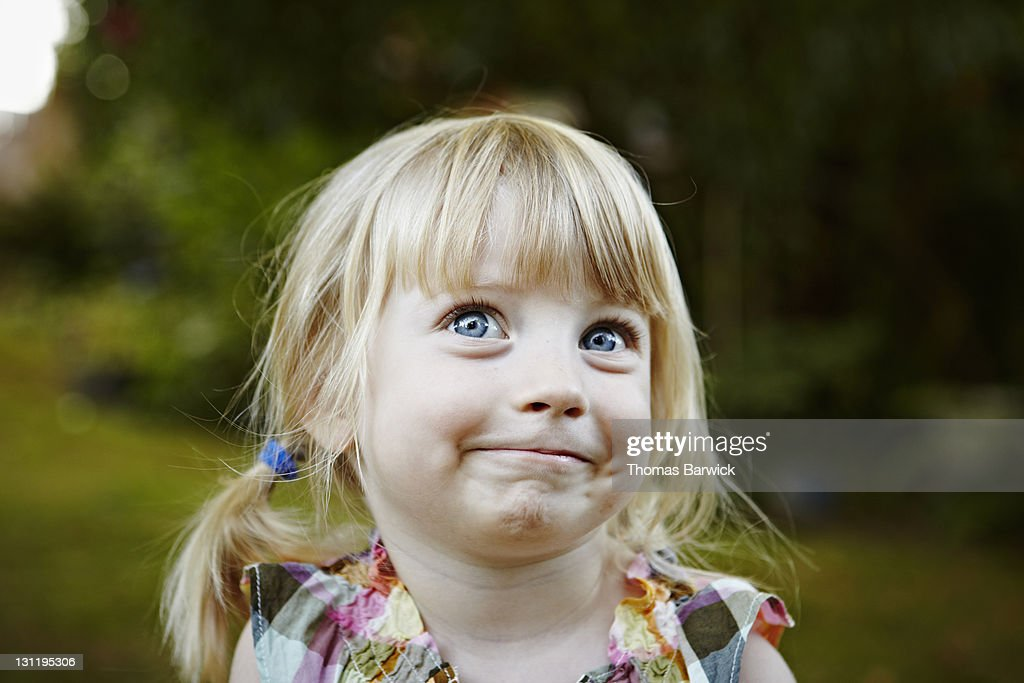 Young girl in backyard smiling looking up : Stock Photo