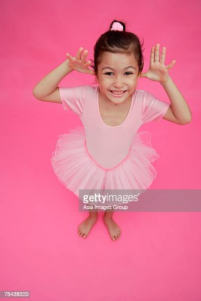 Young girl in ballet outfit, hands on either side of face