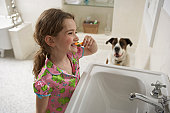 Young girl (8-10) in bathroom brushing her teeth with dog
