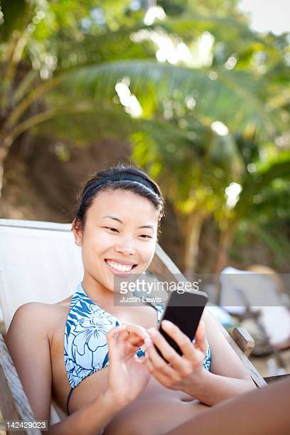 Young girl in beach chair using touch phone