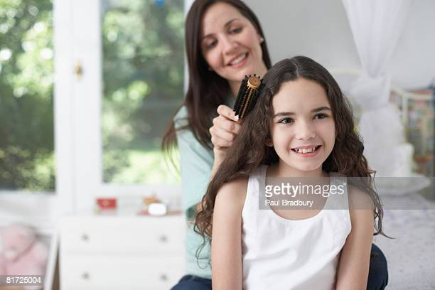 Young girl in bedroom having hair brushed by woman and smiling