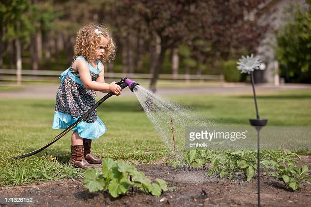 Young Girl In Blue Dress Watering the Garden