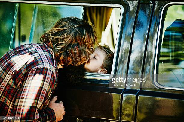 Young girl in camper van kissing father