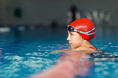 Young girl swimmer resting after training in swimming pool