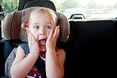 young girl in carseat with shocked expression