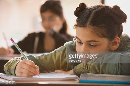 Young girl in classroom doing school work : Stock Photo