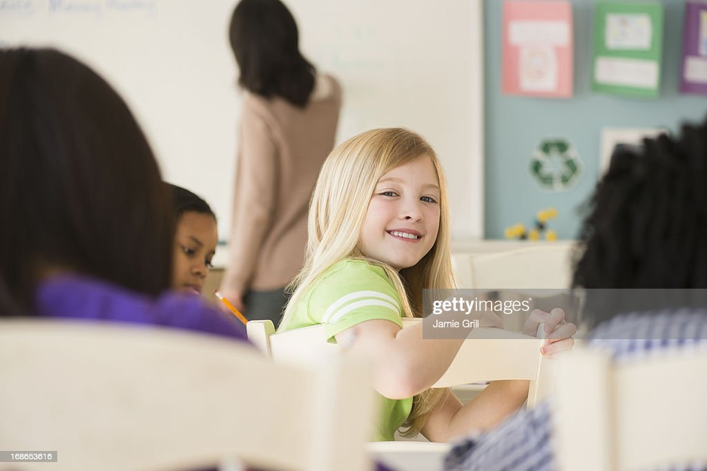 Young girl in classroom, smiling : Stock Photo