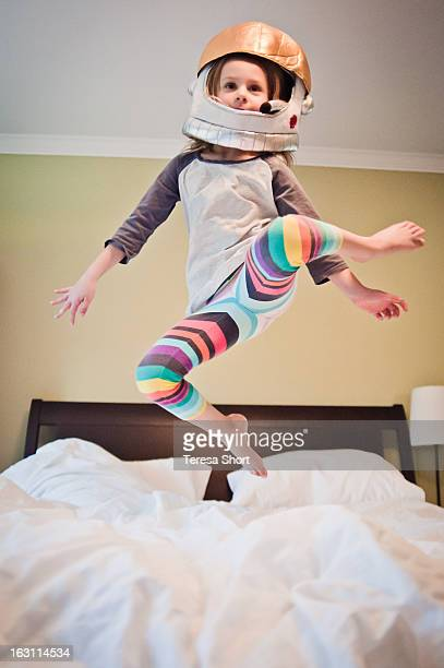 Young Girl in Costume Jumping on Bed