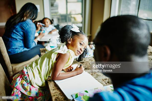 Young girl in discussion with father while drawing