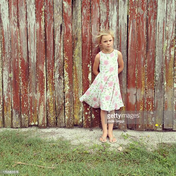 Young girl in dress standing against wooden fence