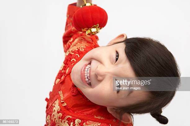 Young girl in festival Chinese New Year clothing, smiling at camera, holding Chinese lantern