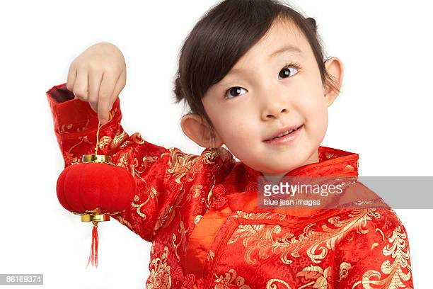 Young girl in festival Chinese New Year clothing, smiling, holding Chinese lantern