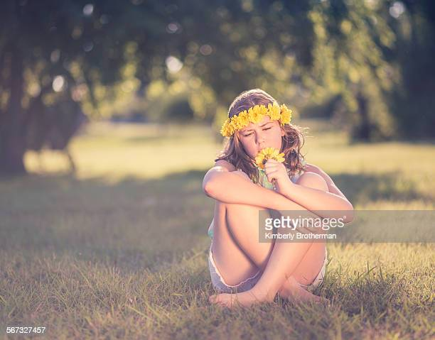 Young girl in flower crown sitting in the grass