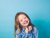 young girl in front of blue background in the studio