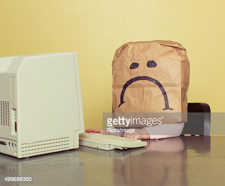 Young Girl in Front of Computer with Brown Bag Frown