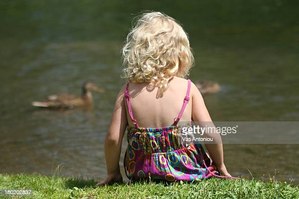 Young girl in front of duck pond